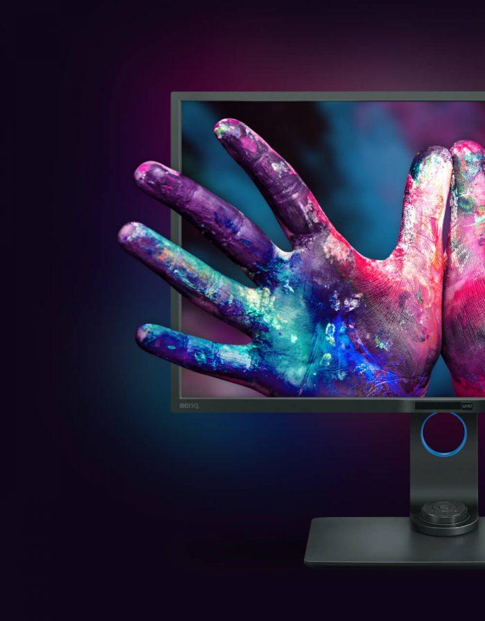 Hände voller Farben die aus einem Bildschirm von BenQ herausragen.