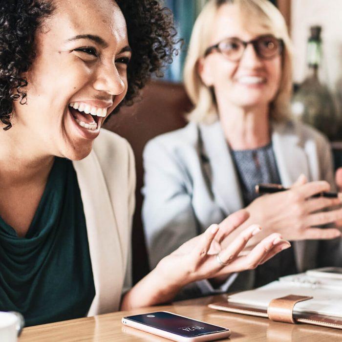 Zwei lachende Frauen sitzend am Tisch bei einem Meeting mit Notizheft und Handy.
