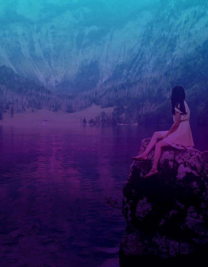 Junge Frau sitzt auf einem Stein am Wasser und schaut auf die Berge.