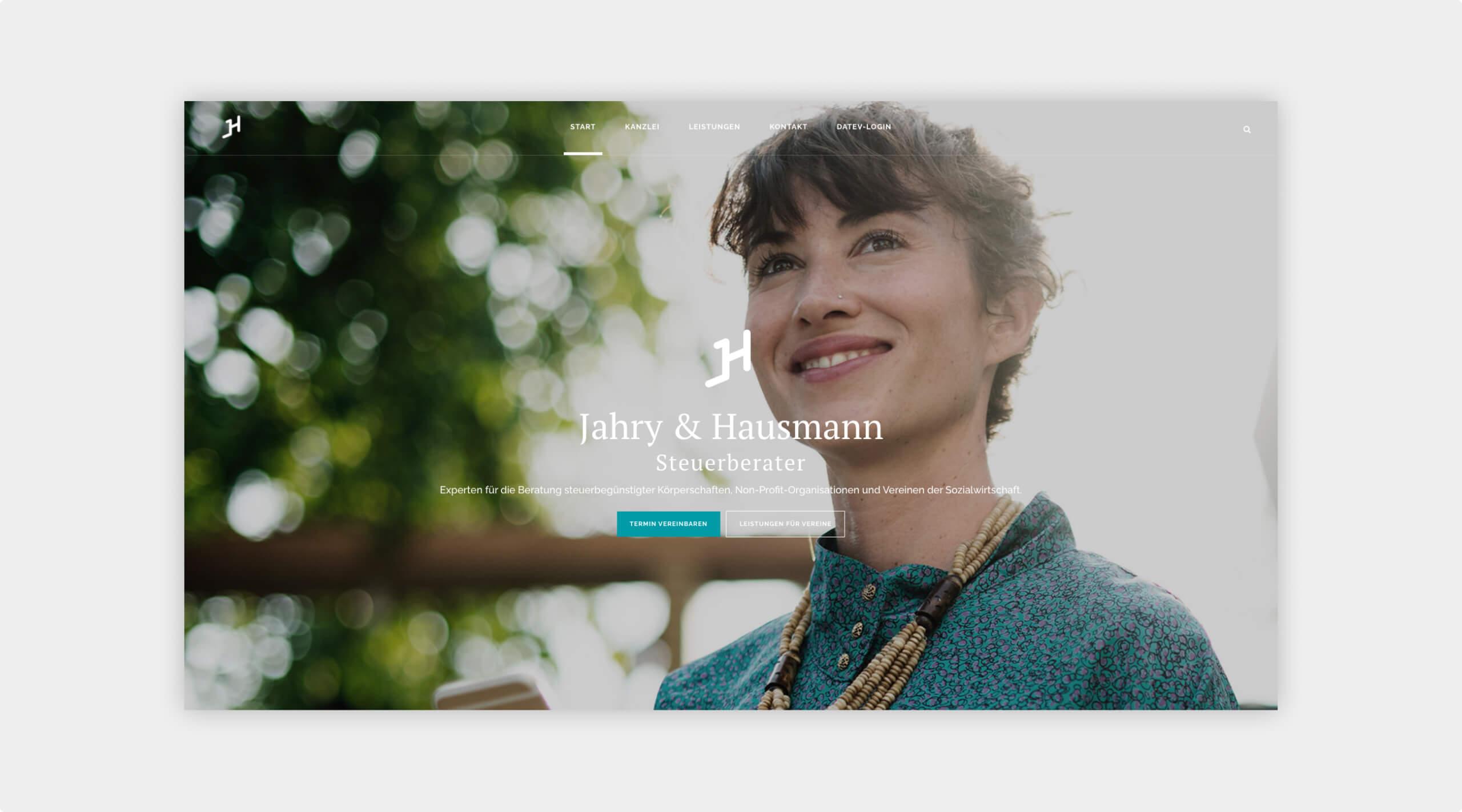 Screenshot der Startseite auf der Website von Steuerberatung Jahry & Hausmann. Lächelnde Frau im Hintergrund mit Logo und kurzem Einleiter in der Mitte.