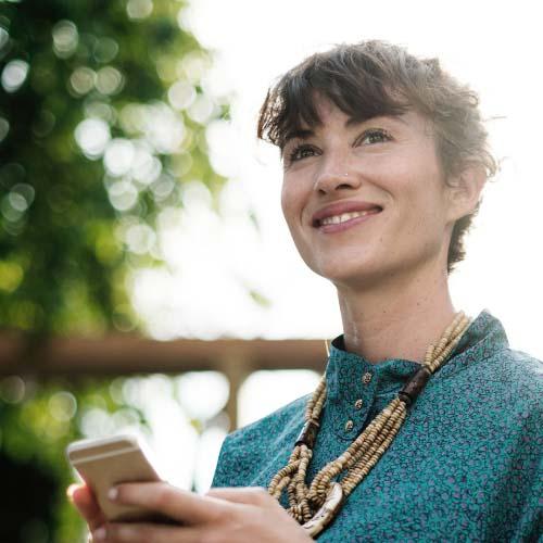 Junge hübsche Frau mit einem Lächeln hält ein Smartphone in der Hand.